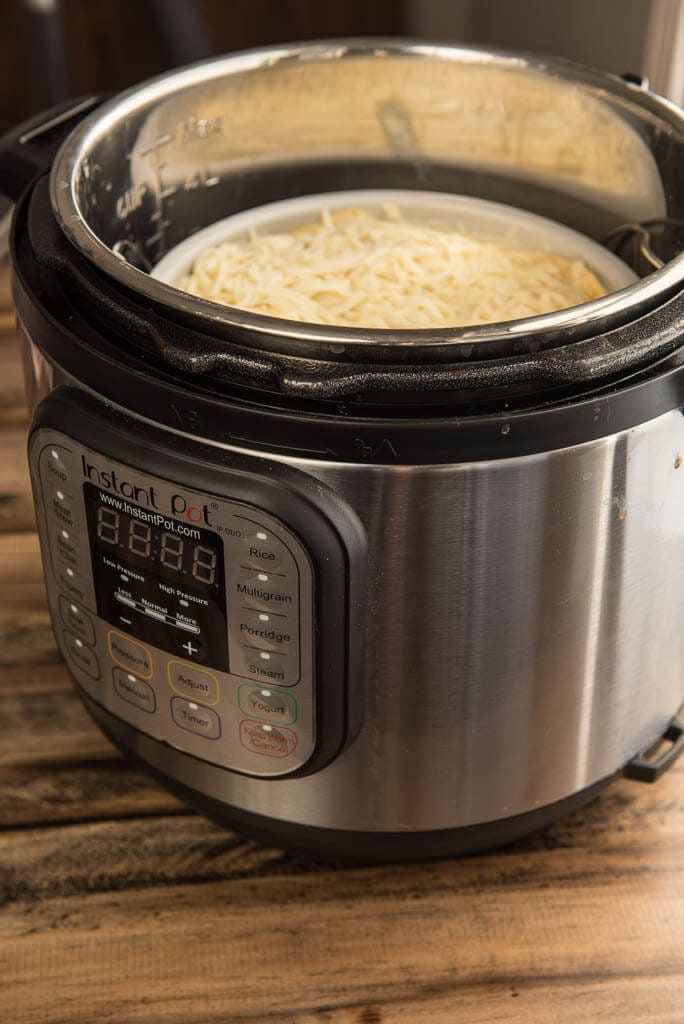 Circular pan of prepared chicken enchilada casserole topped with cheese placed inside the Instant Pot.
