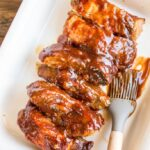 Slow Cooker Country Style Ribs with BBQ Sauce in a red and white casserole dish