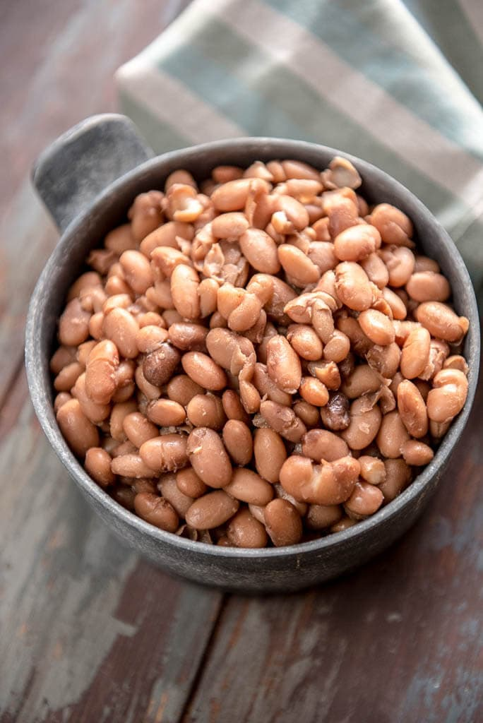 Overhead view of Slow Cooker Pinto Beans in metal bowl on painted table