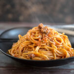 Veggie Packed Instant Pot Spaghetti with Meat Sauce on a black plate with steam