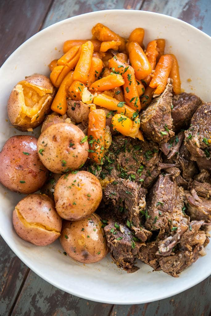Pressure Cooker Pot Roast in white bowl with potatoes and carrots