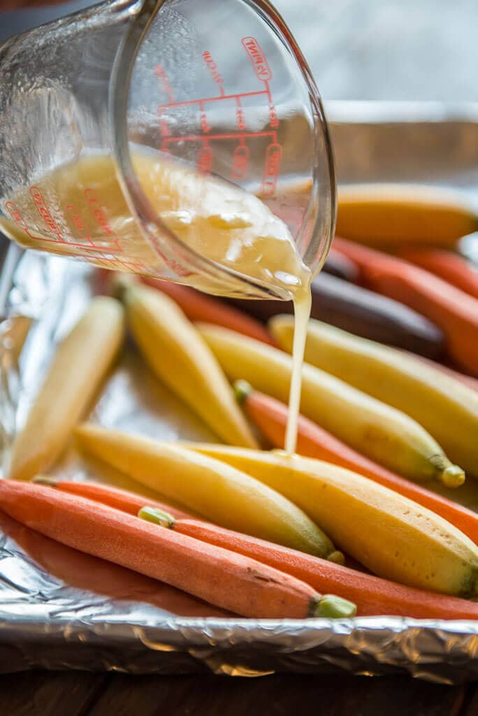 honey butter sauce being drizzled on carrots on baking sheet