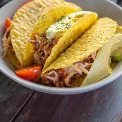 Tacos stuffed with Slow Cooker Salsa Chicken on a gray plate topped with tomato and avocado