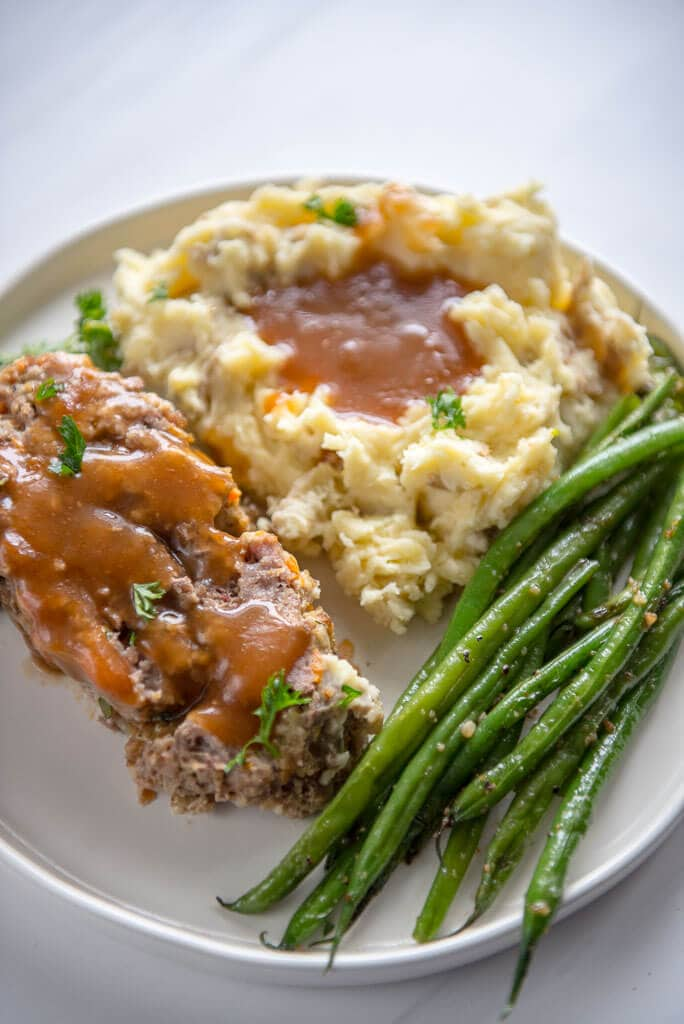 slow cooker meatloaf with buttermilk mashed potatoes and green beans on white plate