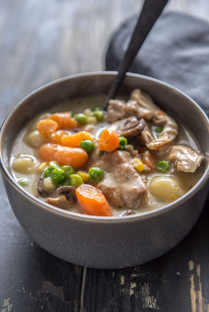 instant pot chicken and dumplings with veggies in gray bowl with black spoon