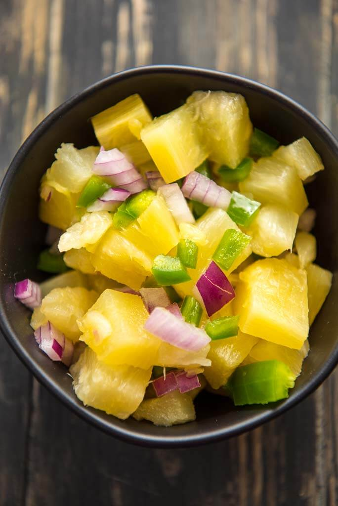 pineapple salsa in a black bowl
