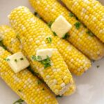6 ears of corn on the cob in a white bowl topped with butter and cilantro
