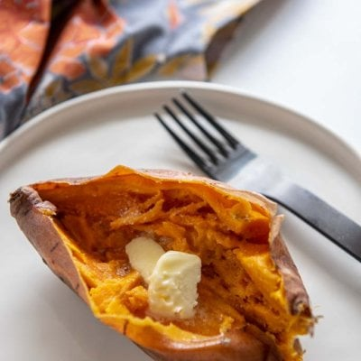 Instant Pot Sweet Potato cut open with butter on top on white plate