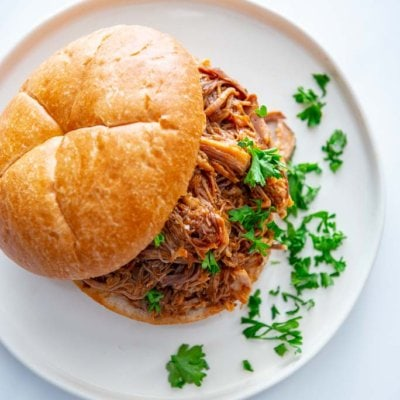 slow cooker bbq pulled pork on a kaiser roll on a white plate with parsley garnish