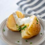 slow cooker baked potato on gray plate cut open topped with butter and sour cream