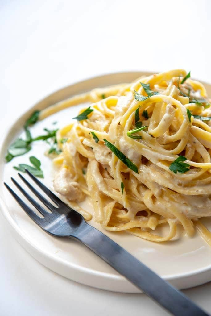 slow cooker chicken Alfredo Pasta twirled on a white plate with a black fork