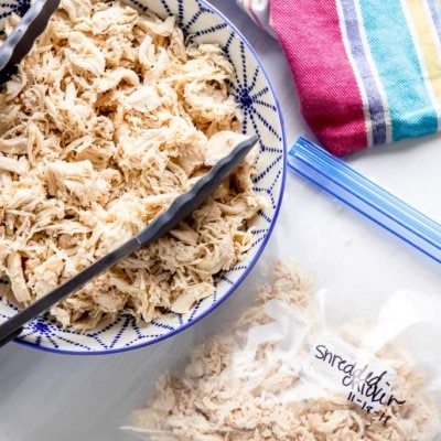 shredded chicken in a blue and white bowl next to freezer bag with shredded chicken and striped towel