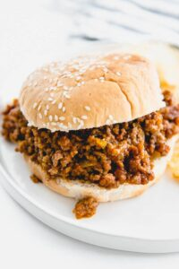 sloppy Joe with sesame seed bun on white plate