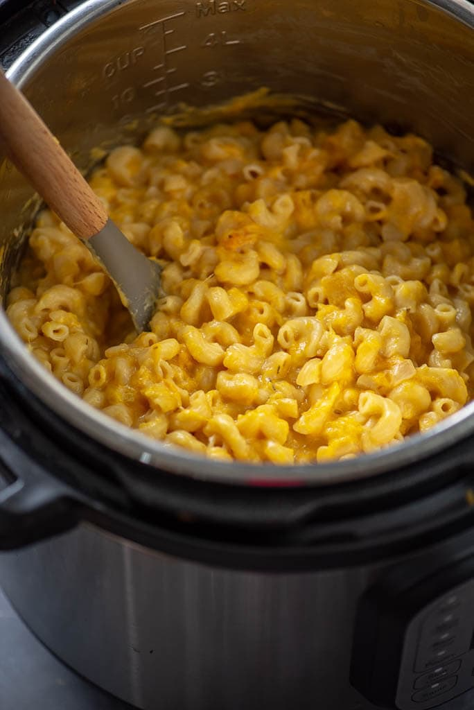 butternut squash Mac and cheese in instant pot with spoon to stir