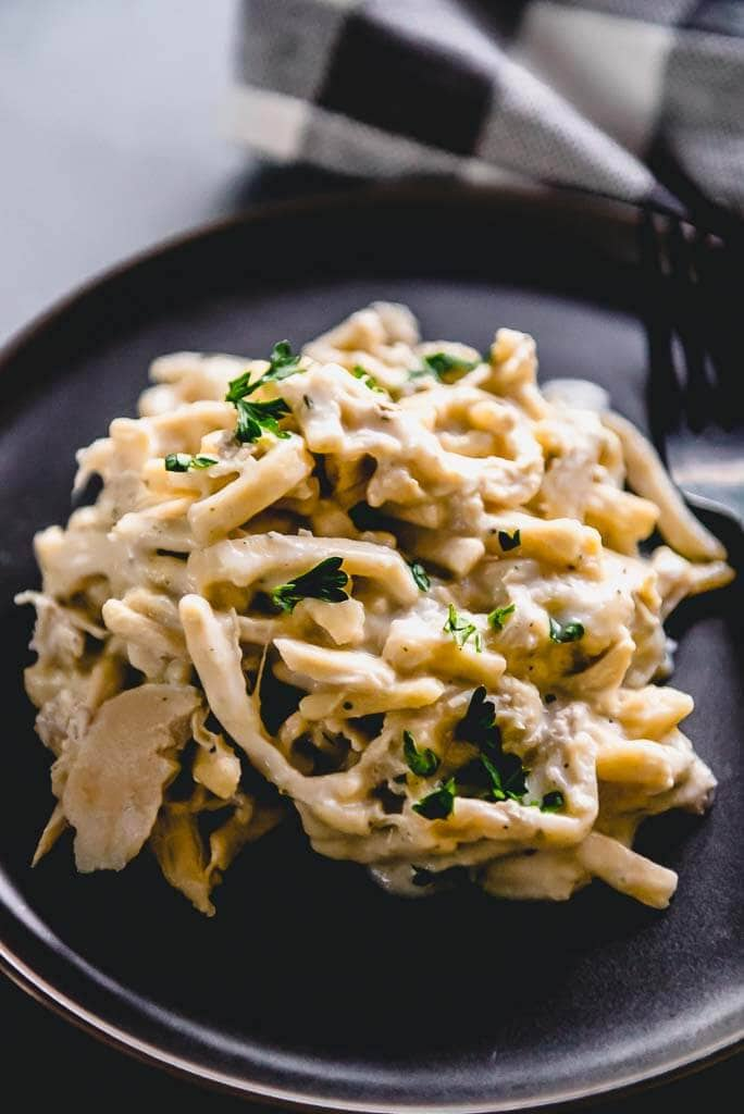 slow cooker chicken and noodles on a black plate with a black fork