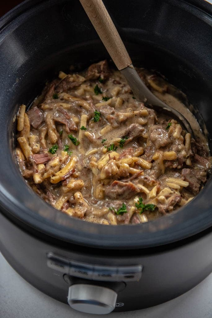 beef and noodles in a slow cooker with a serving spoon