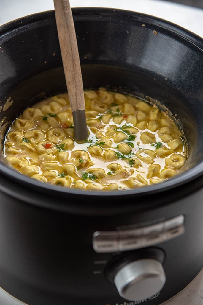chicken tortellini soup in slow cooker with ladle