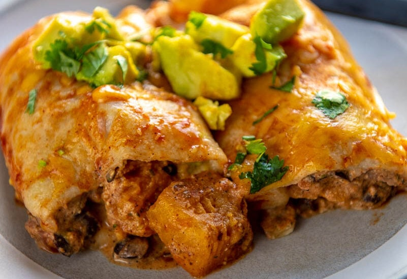 butternut squash enchiladas on a gray and white rimmed plate