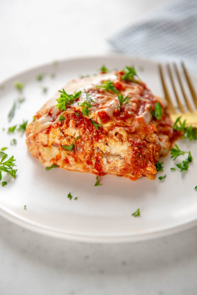 side view of cheesy lasagna layers on white plate