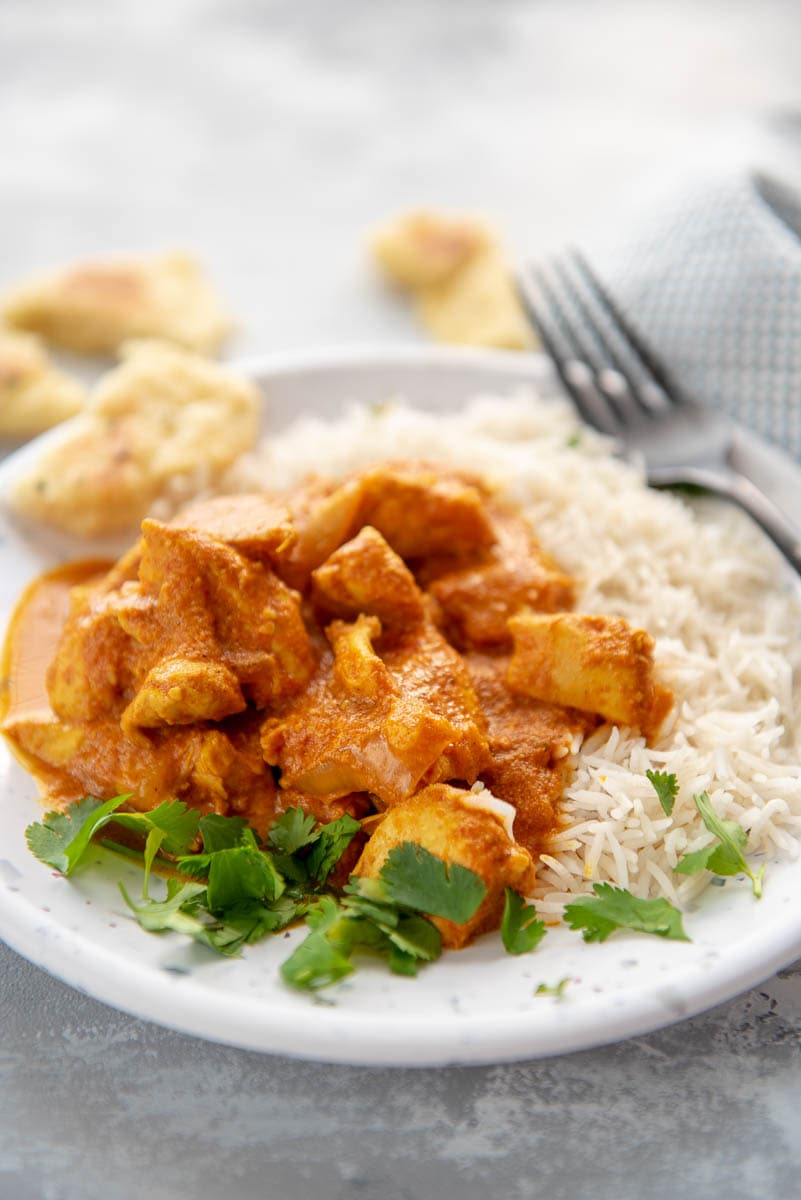 butter chicken with rice on a white plate