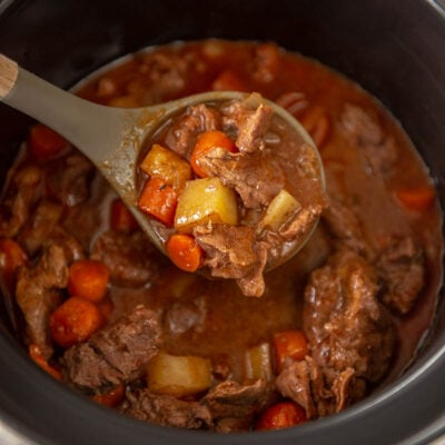 slow cooker with ladle full of beef stew