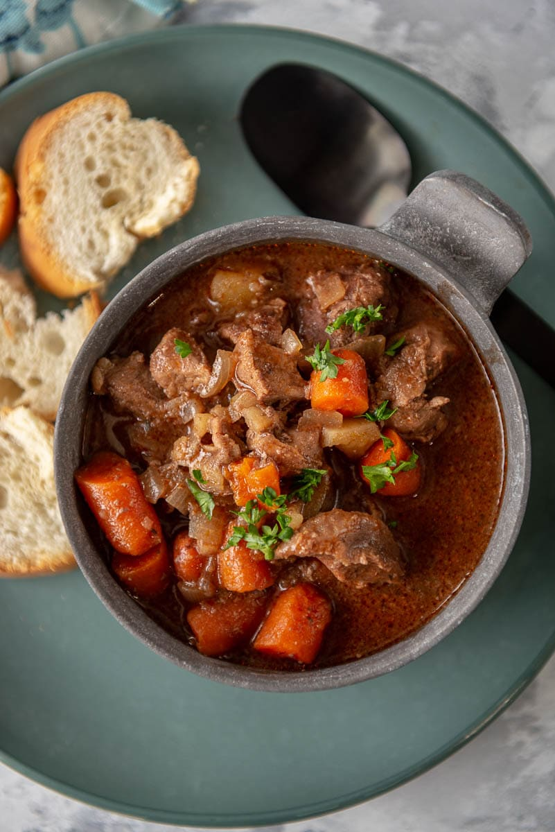 bowl filled with beef stew on a plate with crusty bread