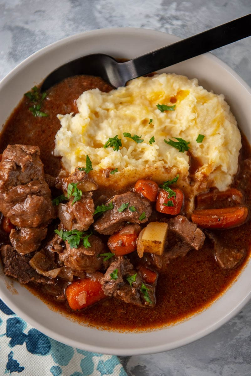 bowl filled with mashed potatoes and beef stew