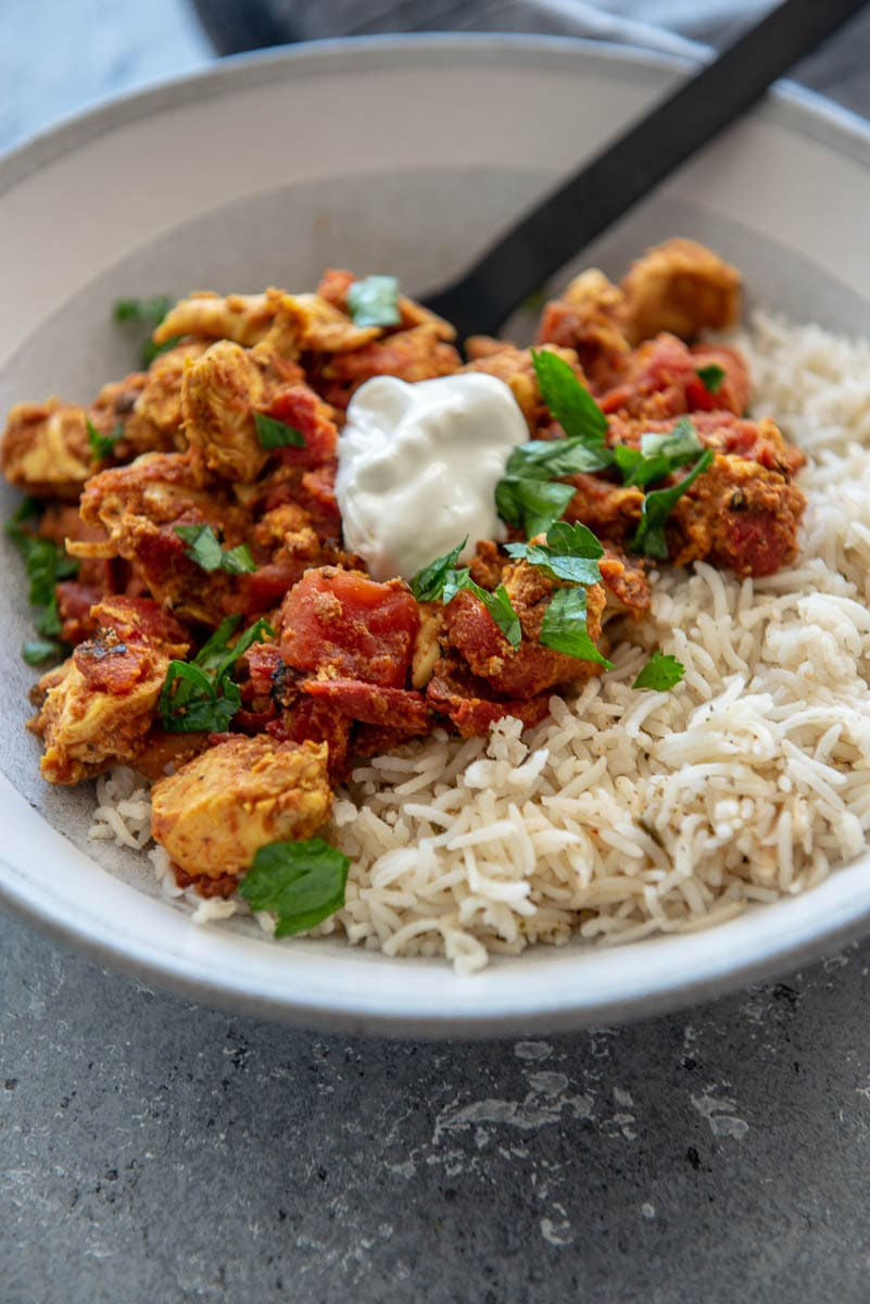 moroccan chicken in gray bowl on rice with sour cream