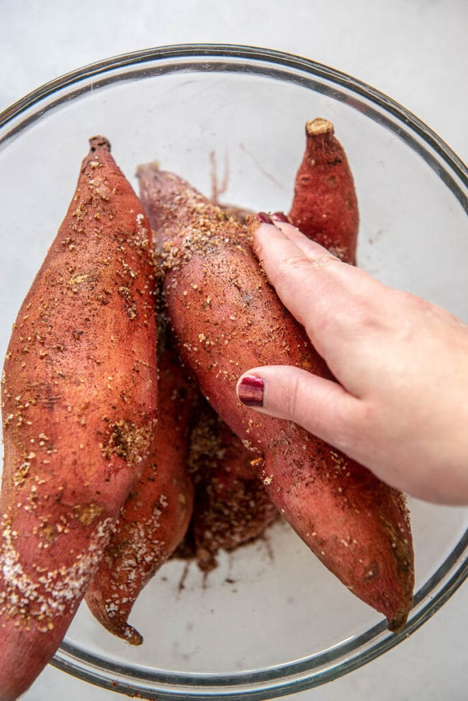 rubbing seasoning into sweet potatoes