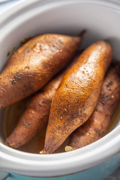 baked sweet potatoes in a white slow cooker