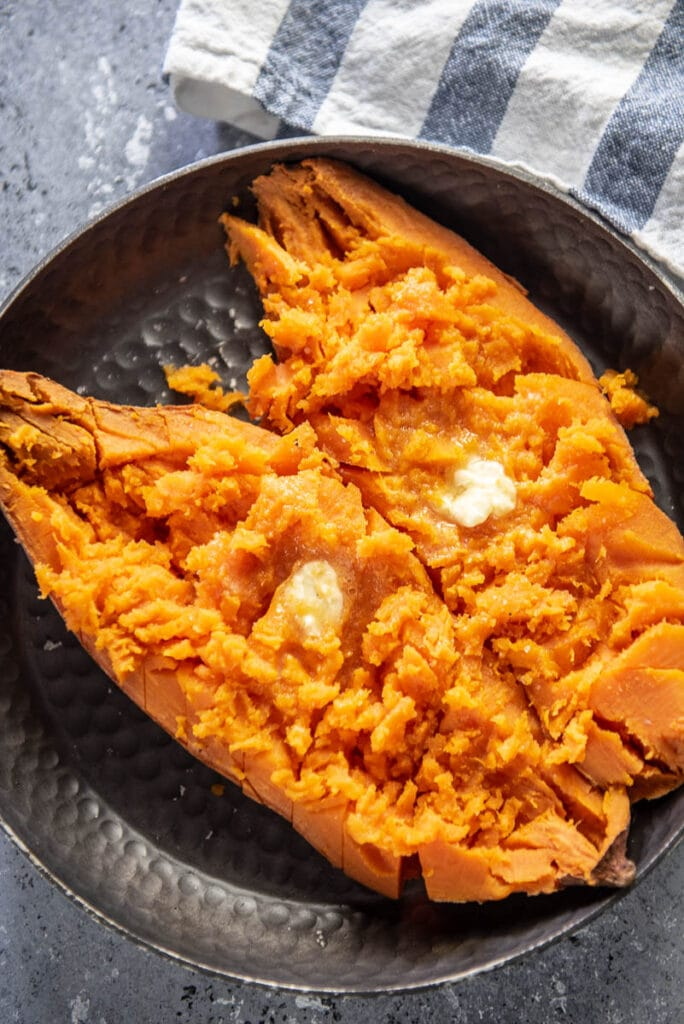 baked sweet potato cut open and topped with butter on plate