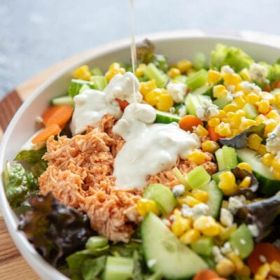 pouring dressing on buffalo chicken salad in bowl