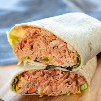 buffalo chicken wrap cut in half on cutting board