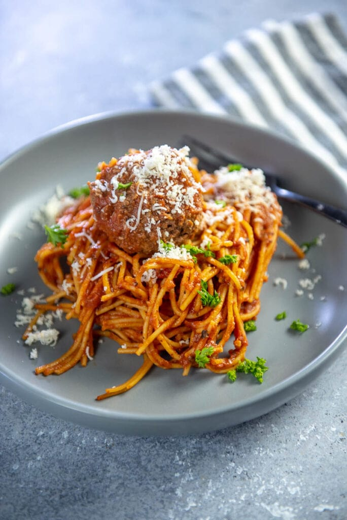 spaghetti and meatballs in a gray bowls