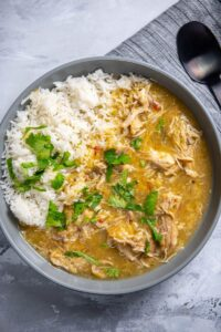 chicken chili verde in large gray bowl with rice and cilantro