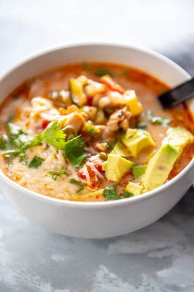 bowl of chicken taco soup topped with cilantro and avocado