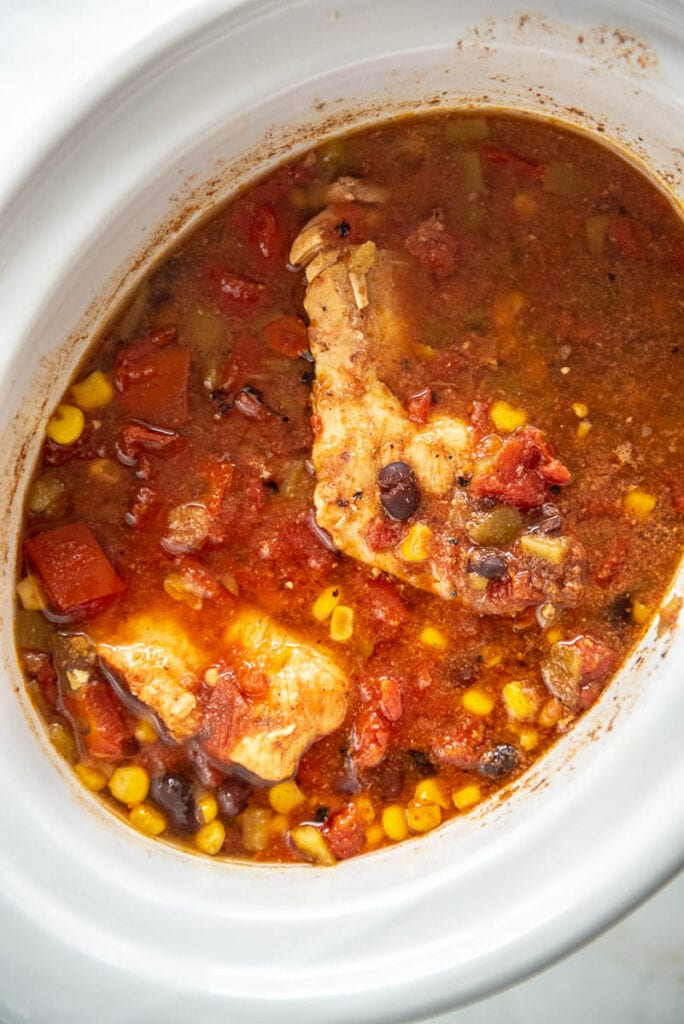cooked mexican chicken with tomatoes in white slow cooker