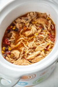 shredded mexican chicken in white slow cooker