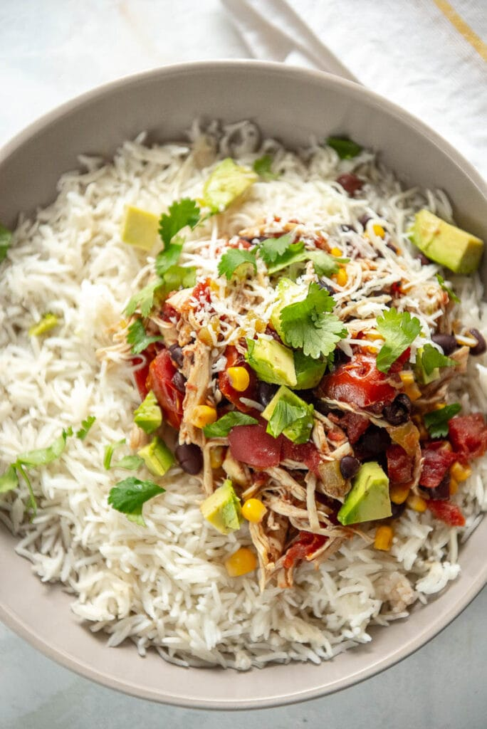 mexican chicken over rice topped with avocado chunks and cilantro in gray bowl