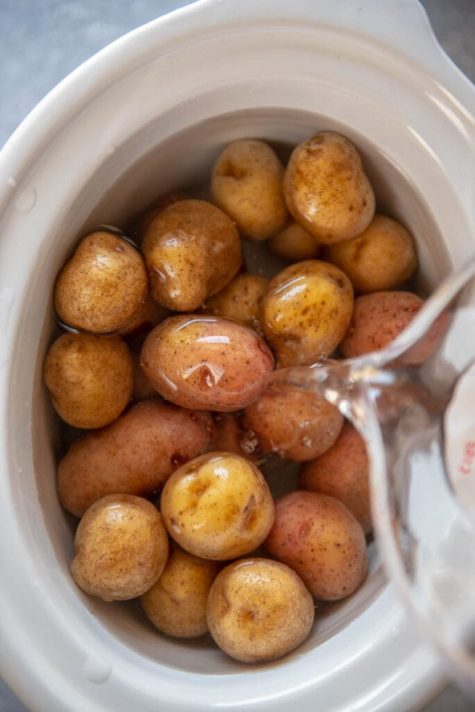 adding water to baby potatoes in slow cooker