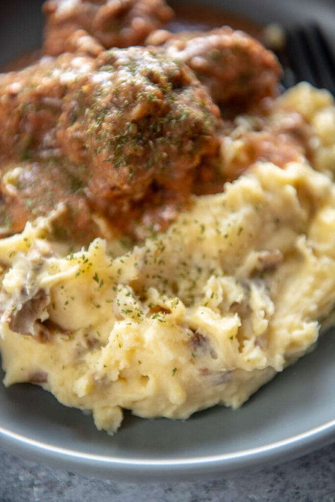 mashed potatoes next to meatballs on plate