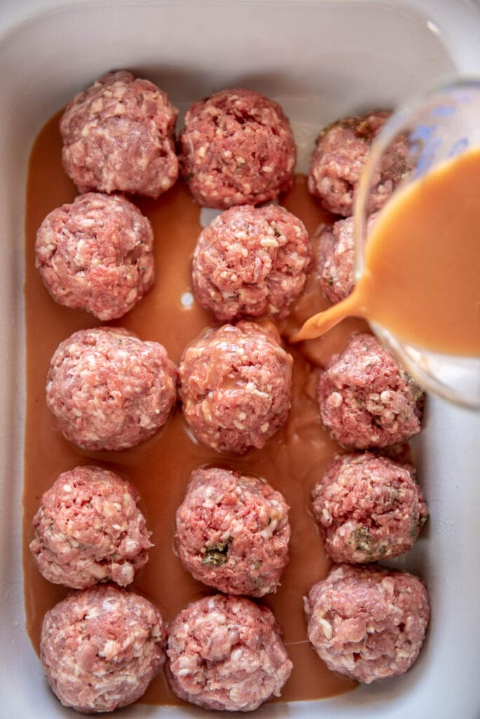 pouring sauce over uncooked meatballs in slow cooker