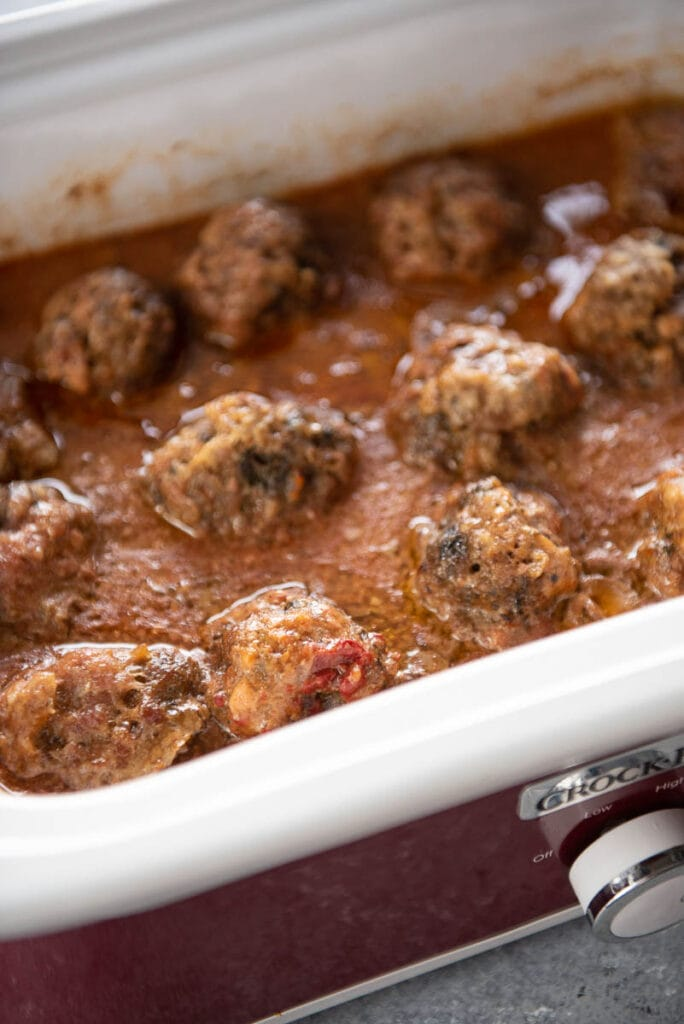 slow cooker of cooked gluten free meatballs with gravy sauce