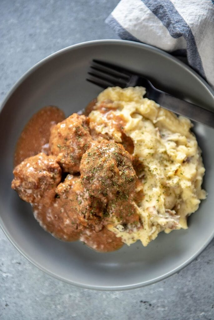 meatballs and mashed potatoes in gray bowl with gravy