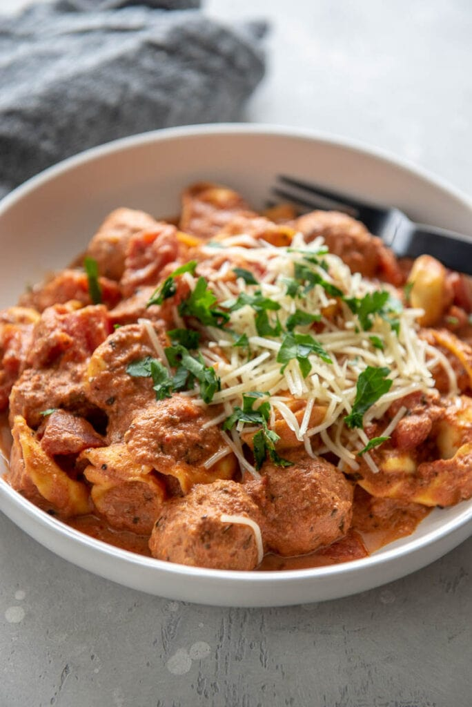 side view of white bowl with meatballs and tortellini in creamy tomato sauce