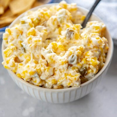 white ridged bowl filled corn dip with jalapeño pieces with chips in background