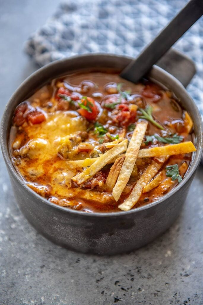 chili in a metal bowl topped with tortilla strips
