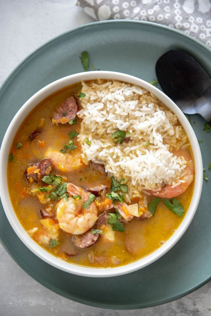 overhead view of shrimp and sausage gumbo in white bowl on green plate