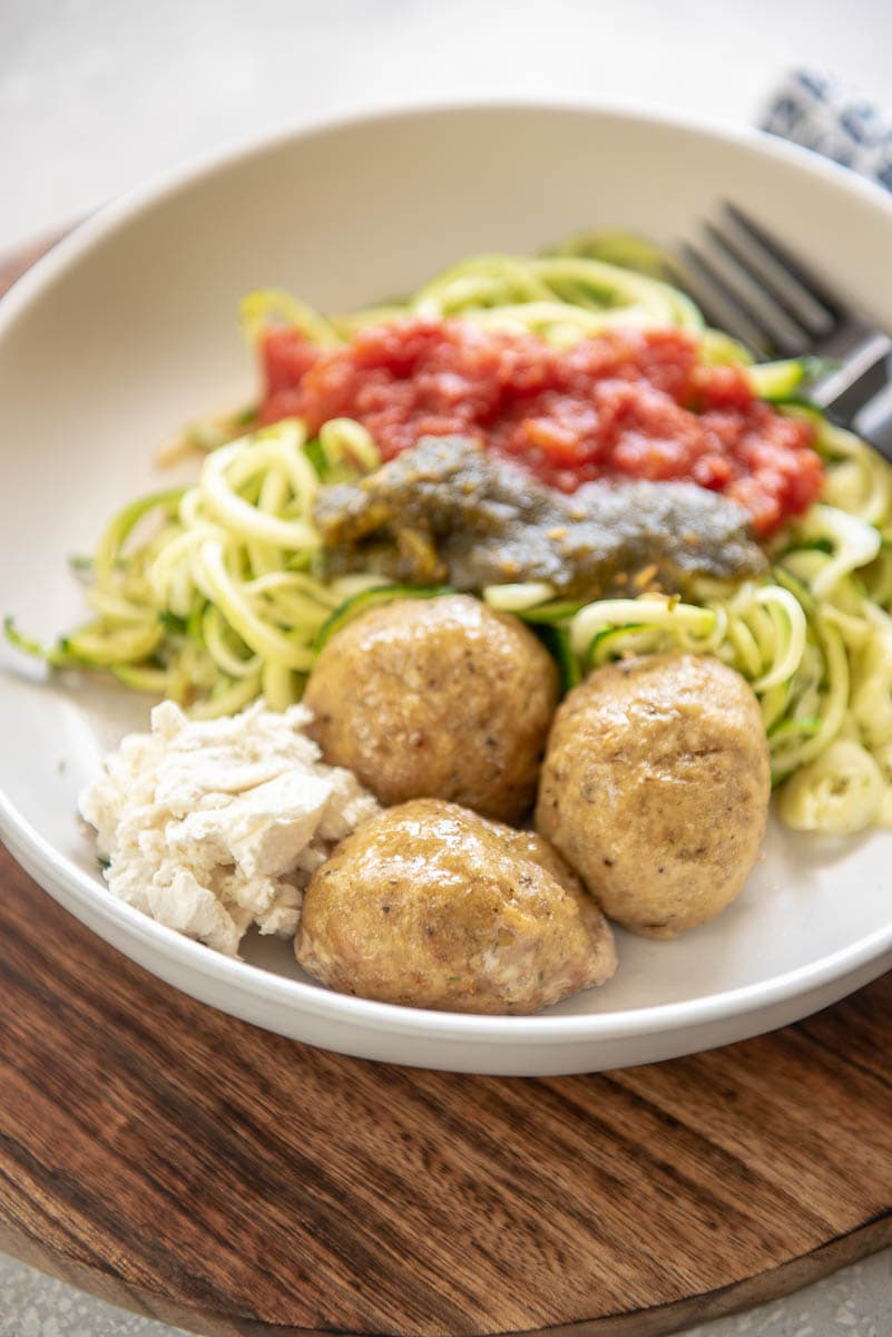 turkey meatballs on a white plate with noodles, marinara, and pesto
