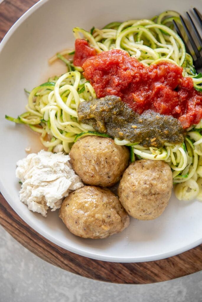 turkey meatballs on a plate with zucchini noodles, marinara, and pesto